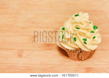 Birthday vanilla cupcake muffin with butter cream icing topping isolated on cutting board wooden brown background. Sweet home baked single cake dessert with small fir-trees sprinkles on top.