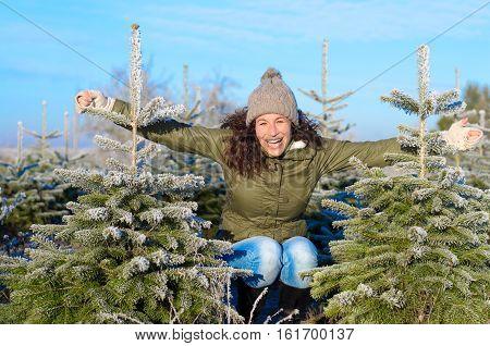 Vivacious Woman Posing Between Christmas Trees