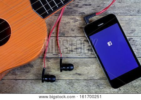 BUNG KAN THAILAND - OCTOBER 25 2015: Smart phone and Guitar earphones and smart phone and facebook app on screen