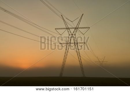 Power pylons in the sunset on a misty evening