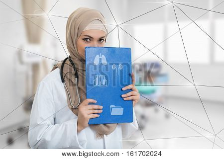 portrait of worried muslim female Medical doctor holding paperclip at hospital.