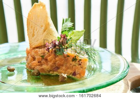 A dish of salmon tartare, red and green onions, lemon zest and olive oil served on a plate