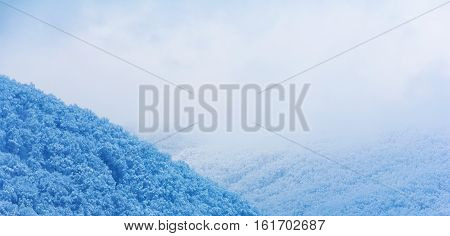 snow-covered hills in the clouds in the early winter morning in the foothills of the Caucasus. Shallow depth of field photo toning