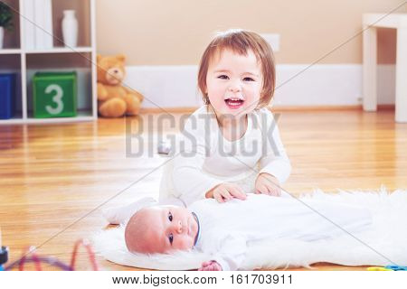 Happy Toddler Girl With Her Newborn Sister