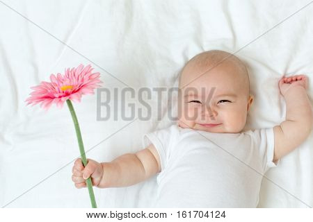 Happy Newborn Baby Girl Playing With A Flower