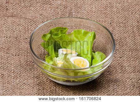 Boiled eggs in bowl on sackcloth. Food background