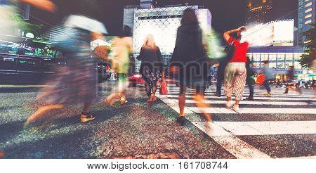 Motion Blurred People Walking In The City At Night