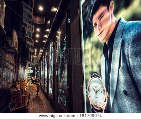 HONG KONG - October 2016: Little alley with people and glowing advert at night. Causeway Bay