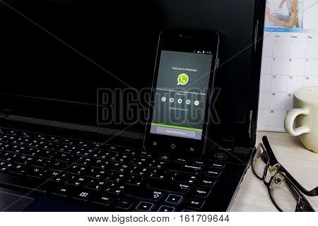 BUNG KAN THAILAND - APRIL 04 2016: smart phone display whatsapp app on notebook in the office with a cup of coffee