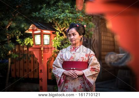 TOKYO, JAPAN - NOVEMBER 10, 2016: Young woman wearing traditional japanese kimono walk on the street of Gion, Kyoto old town, Japan. Kimono is a Japanese traditional garment.