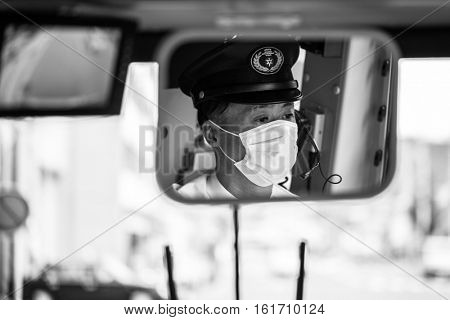 KYOTO, JAPAN - NOVEMBER 11, 2016: Kyoto city bus driver wearing mask at work, Japan. Buses are the main public transportation system in Kyoto.