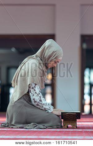 Young muslim woman reading koran in mosque.