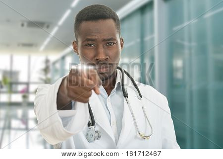 Angry african black male doctor pointing finger at you with stethoscope around his neck, pointing at camera with serious facein modern hospital