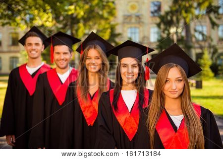 Successful Confident  Five Graduates In Robes And Hats With Tassel Smiling