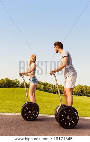 Portrait Of Happy Man And Woman Riding Electric Segway In Park
