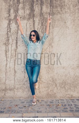 Hey! Cheerful Positive Brunette Posing Near Stone Wall And Raised Hands Up