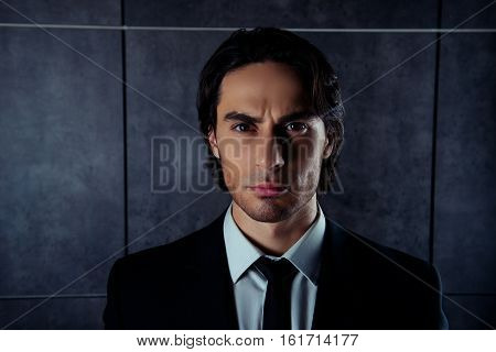 Portrait Of Serious Brutal Man In Formalwear On Gray Background