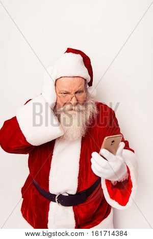 Confused Santa Claus Wearing Red Costume Reading Messege On Phone  While Standing White Background