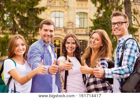Diverse Five Joyful Friends Showing Thumbs Up Standing Near Campus