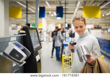 Pretty, young woman using self service checkout in a store (shallow DOF; color toned image)