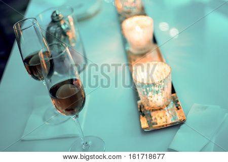 Two champagne glasses celebration anniversary background with rose sparkling on table with romantic golden candlelight and Christmas new years winter wonderland decorations