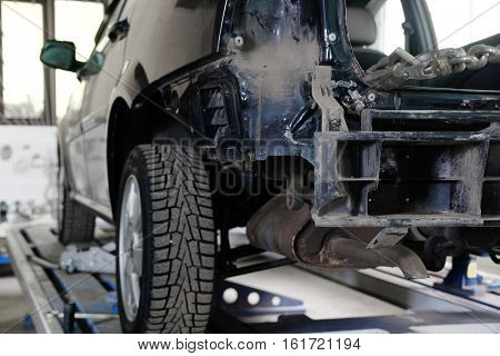 Black crashed car on stocks in a car repair station