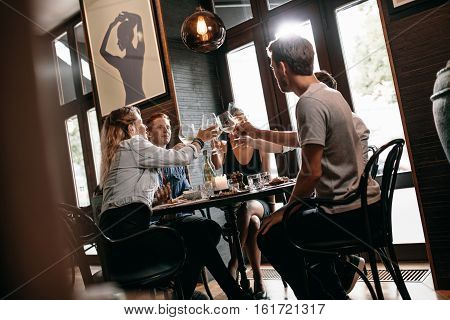 Group of friends toasting wine at restaurant. Young man and woman sitting at table and toasting drinks at cafe.