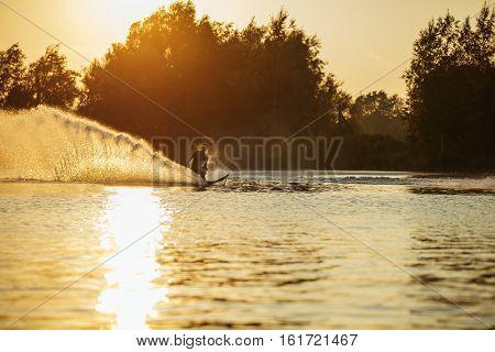 Man water skiing on lake with splashes of water. Man wakeboarding at sunset.