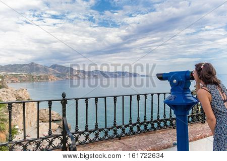 Girl looking through a telescope in Nerja, Malaga, Spain