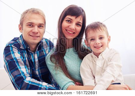 Close-up of elated family at home. Sitting on a sofa. Young family in casual clothes relaxing at home. The concept of happy family