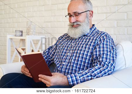 A mid shot of an elderly smiling beard male reading a book in red cover. Smiling man wearing glasses
