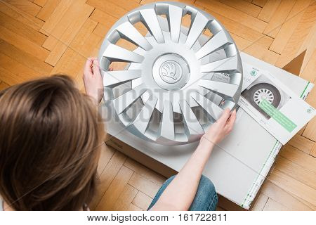PARIS FRANCE - DEC 7 2016: Woman holding unboxing unpacking modern hub covers for the winter tyres made by Skoda Auto - good deal online internet shopping