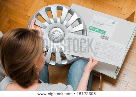 PARIS FRANCE - DEC 7 2016: Woman unboxing unpacking modern hub covers and reading instruction for the winter tyres made by Skoda Auto - online internet shopping