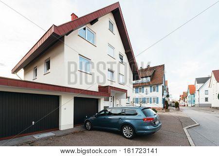 FREUDENSTADT GERMANY - NOV 20 2016: Modern Hybrid Volkswagen Passat wagon car parked on the German street with german architecture in the background