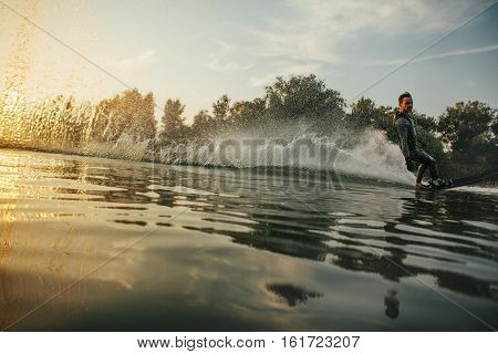 Water surface level shot of wakeboarder skiing on lake at sunset. Water skiing on lake.