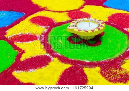 Indian earthenware and wax lamp, diya, set in the center of a colorful ground painting called rangoli. Usually put in the hindu festival of Diwali