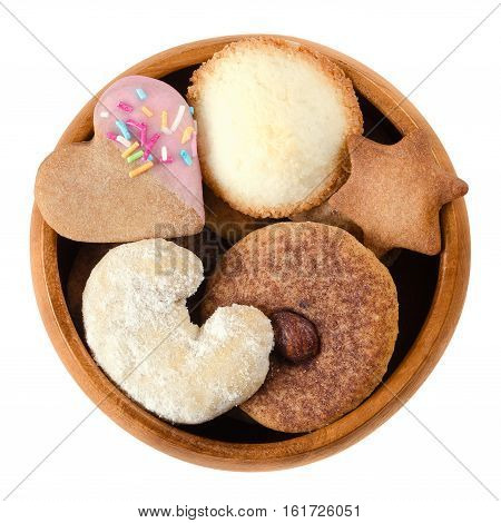 Cookies and biscuits in wooden bowl. Assorted flat sweet baked goods in heart, crescent, star and disc shapes with different decor. Isolated macro food photo close up from above on white background.