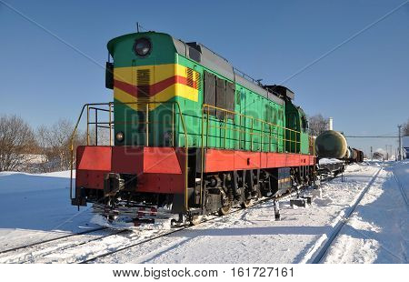 Shunting diesel locomotive on the tracks. Winter.