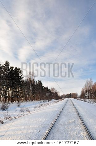 One way railroad. The railroad goes into the distance. Snow in the winter.
