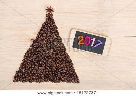 Christmas tree made from coffee beans and phone on a wooden background. Top view, copy space.Winter holidays concept. 2017 colorful numbers.