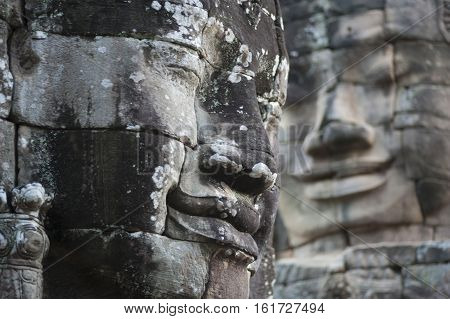A horizontal photographic image of two large sculpted stone faces of the Buddha at Bayon Temple in Angkor Thom which is close to Angkor Wat near Siem Reap in Cambodia.