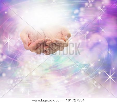 Divine Light Healing Energy - female hands cupped with a ball of bright energy above on a beautiful sparkling purple pink bokeh energy field background with plenty of copy space
