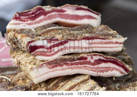 Pieces of smoked bacon on a street stand