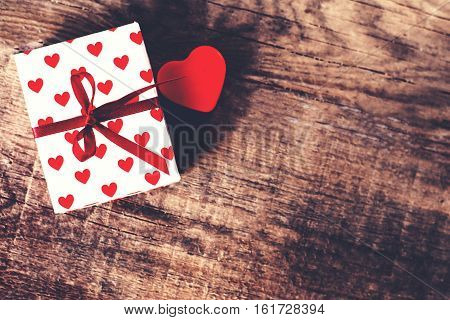 Valentines Day background with red heart and present gift on wooden background with blank copy space