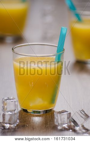 Freshly squeezed orange juice in glass with blue straw and ice cubes. Selective focus on front glass and straw.
