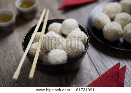 Homemade chinese Tang Yuan dumplings with coconut sprinkles in black bowl served with green tea. Selective focus. Concept of contemporary chinese food.
