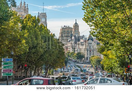 View from Plaza de la Independenci, Madrid, to Metropolis building.  Busy, bustling mid-day street scene.  Spain urban life, traffic & cars in foreground.