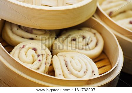 Homemade chinese steamed bread buns Mantou with red onions sesame oil and pepper prepared in bamboo steamer. Concept of chinese cuisine. Concept of asian food. Selective focus on middle of left front bread bun.