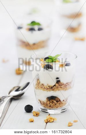 Delicious homemade dessert granola and blueberry yogurt parfait in glass with mint on white wood boards. Concept of light dessert. Concept of comfort food