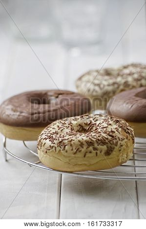 Sweet homemade dessert doughnuts with white and milk chocolate in rustic setting on white wood boards and glasses of milk and milk bottle. Selective focus on front doughnut.
